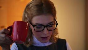 Müde Geschäftsfrau, die spät an Computer und trinkendem Kaffee im Büro arbeitet stock video footage
