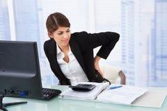 Müde Geschäftsfrau, die unter Rückenschmerzen leidet stockfotografie