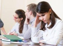 Müde Geschäftsfrau mit Kopfschmerzen auf Seminar Stockfoto