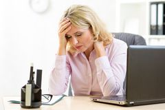 Müde Geschäftsfrau von mittlerem Alter in ihrem Büro Stockbilder