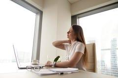 Müde Geschäftsfraugefühlsnackenschmerzen nach langer Arbeit über Berechnung Stockfotos