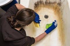 Müde Hausfrau, die alte schmutzige Badewanne säubert lizenzfreie stockbilder