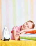Müde Hausfrau schlief auf Bügelbrett mit Eisen ein Stockbild