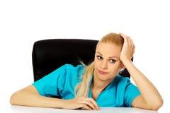Müde junge Ärztin oder Krankenschwester, die hinter dem Schreibtisch sitzen stockfotos