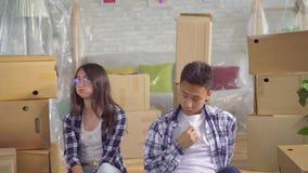 Müde junge asiatische Paare beim Bewegen auf neue Wohnung stock video
