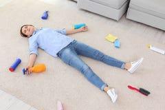 Müde junge Frau, die auf dem Teppich umgeben durch Putzzeug liegt lizenzfreie stockfotografie
