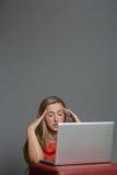 Müde junge Frau, die an einem Laptop arbeitet Stockbilder