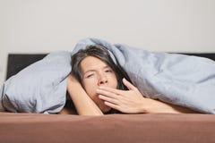 Müde junge Frau, die unter einer Daunendecke gähnt Stockfoto
