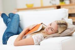 Müde junge Frau, die zu Hause ein Schläfchen hält Lizenzfreie Stockfotografie