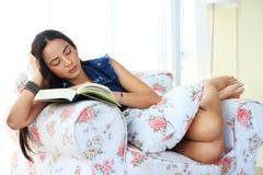 Müde junge Frau, die zu Hause liegend auf Sofa mit einem Buch ein Schläfchen hält Stockfotografie