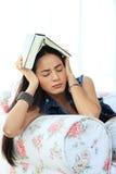 Müde junge Frau, die zu Hause liegend auf Sofa mit einem Buch ein Schläfchen hält Stockfotos