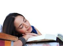 Müde junge Frau, die zu Hause liegend auf Sofa mit einem Buch ein Schläfchen hält Lizenzfreie Stockbilder