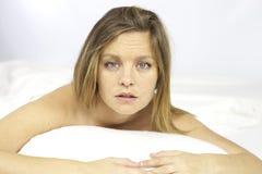 Müde junge Frau im Bett Lizenzfreie Stockfotografie
