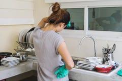 Müde junge Frau mit den Handschuhen, die Teller waschen stockfoto