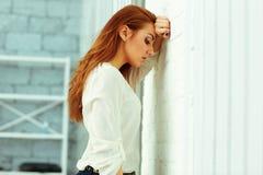 Müde junge Geschäftsfrau, die an der Wand leaing ist lizenzfreie stockbilder