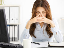 müde junge Geschäftsfrau, die im Büro arbeitet stockbilder