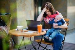 Müde junge Mutter, die oh ihren Laptop bearbeitet Stockfotos
