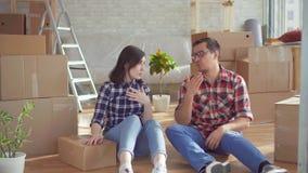 Müde junge Paare mit Laptop auf dem Hintergrund von Kästen für das Bewegen stock video