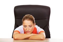 Müde junge weibliche doctoror Krankenschwester, die hinter dem Schreibtisch sitzt lizenzfreies stockfoto
