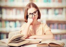 Müde lustige Studentin mit Glaslesebüchern Stockfoto