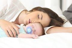 Müde Mutter, die mit ihrem Baby schläft lizenzfreie stockfotografie