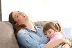 Müde Mutter, die mit ihrer Babytochter schläft lizenzfreies stockbild