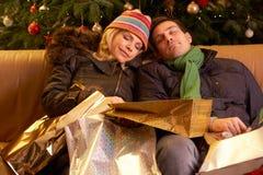Müde Paare, die nach dem Weihnachtseinkaufen zurückgehen lizenzfreies stockfoto