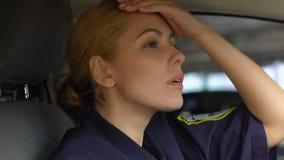 Müde Polizeibeamtin, die Hut nach Aufgabe im Gruppenauto, erschöpfende Arbeit entfernt stock video footage