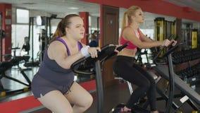Müde pralle Frau mit Magenfett Reitenbemühungen eines Standrads schließlich stock footage