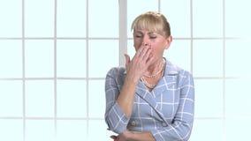 Müde reife gähnende und ausdehnende Frau stock footage