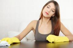 Müde Reinigungsmöbeltabelle der jungen Frau lizenzfreie stockfotos