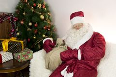 Müde Santa Claus sitzt auf dem Sofa Stockfotografie