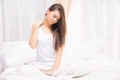 Müde schläfrige Frau, die mit einer Ausdehnung beim Sitzen im Bett aufwacht und gähnt stockfotografie