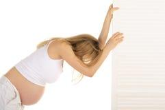 Müde schwangere Frau lehnte sich auf der Tür Stockfoto