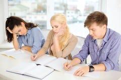 Müde Studenten mit Notizbüchern in der Schule Lizenzfreie Stockbilder