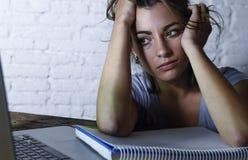 Müde Studentenfrau, die an Laptop-Computer mit dem frustrierten und erschöpften Studieren des Notizblockgefühls für die Prüfung S Stockfotos