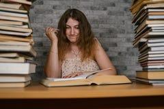 Müde Studentinlesung unter Büchern Nachdenkliche junge Frau, die bei Tisch mit Stapel des Buches sitzt und an liest stockbild