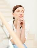 Müde und deprimiert. Schöne junge Ärztin, die am Th sitzt Lizenzfreie Stockbilder