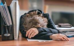 Müde und erschöpfte Workaholicfrau, die auf Schreibtisch im Büro schläft stockfotos