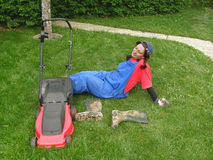 Müde und glückliche Frau, die auf dem Gras sitzt Lizenzfreie Stockbilder