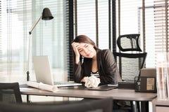 Müde und schläfrige junge Geschäftsfrau am Schreibtisch Lizenzfreies Stockfoto