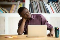 Müder AfroamerikanerBüroangestellter, der unter Nackenschmerzen leidet stockfotos