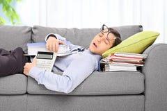 Müder Angestellter, der auf einem Sofa in einem Büro schläft Lizenzfreie Stockbilder