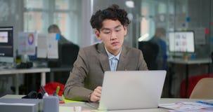 Müder asiatischer junger Programmierer, der weg von den Gläsern sich setzt stock video