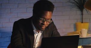 Müder Büroangestellter, der an dem Laptop an Spät- arbeitet Ein Geschäftsmann ist im Büro allein Workaholic, die Frist stock video footage