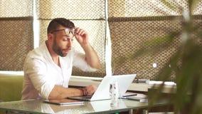 Müder Büroangestellter, harte Arbeit Der Mann wachte auf und fing wieder an, für einen Laptop schwer zu arbeiten Reibt seine Auge stock footage