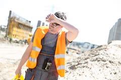 Müder Bauarbeiter, der Stirn am Standort abwischt lizenzfreie stockfotos