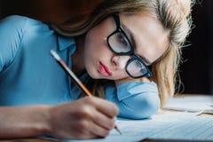 Müder blonder kaukasischer Student in den Brillen, die an Hand liegen und etwas mit Bleistift schreiben Stockbild
