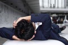 Müder deprimierter junger asiatischer Geschäftsmann, der sich hinlegt und stressig sich fühlt Lizenzfreie Stockbilder