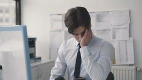 Müder durchdachter Mann, der deligently mit PC im Büro arbeitet 4K stock video footage